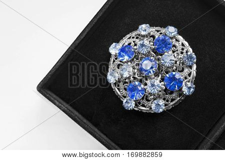 Silver medallion with blue gems in black jewel box closeup