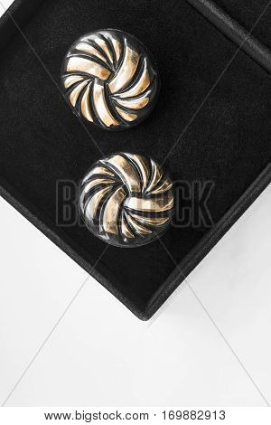 Pair of golden cufflinks in black jewel box closeup