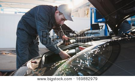 Mechanic male in automobile garage checking hood of luxury sportcar, horizontal