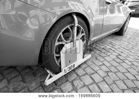 Car clamped on cobbled street