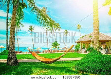 Beautiful Maldive resort and hammock. Empty hammock between palms tree. Summer holiday and vacation concept.