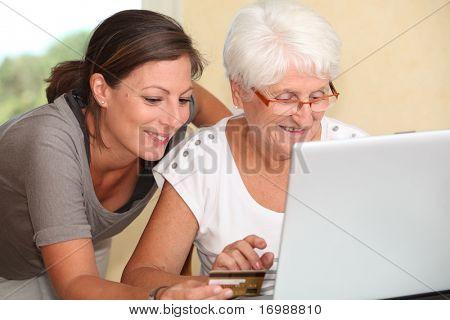 Ältere Frau und junge Frau, die im Internet einkaufen