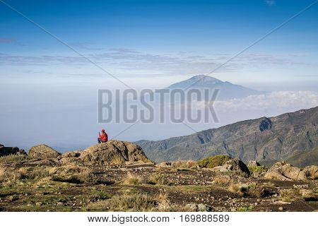 Man siting with his phone with view on Mount Meru Tanzania