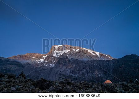 Morning sun illuminates Kibo and tent of hikers Mount Kilimanjaro Tanzania