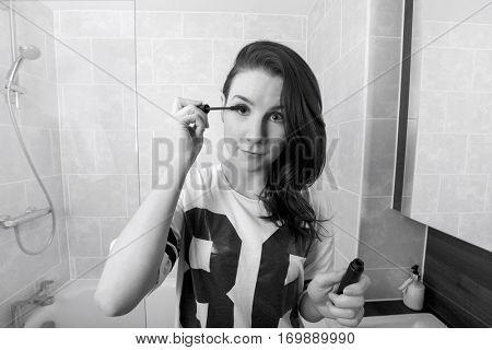 Portrait of beautiful woman applying mascara in bathroom