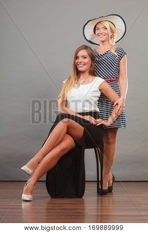 Fashionable style clothes concept. Woman sitting on chair wearing white top and long black shirt showing her leg standing next to older female with short striped dress