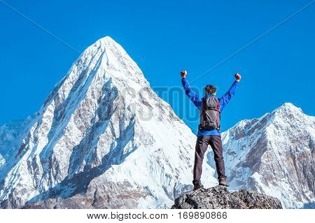 Hiker with backpacks reaches the summit of mountain peak. Active sport concept.