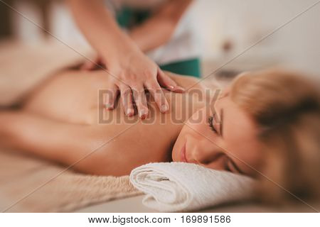 Woman enjoying during a relaxing massage at the spa.