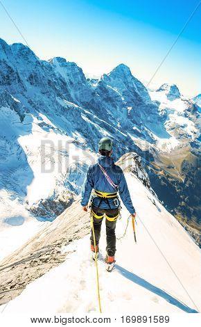 Alpine climber balances on the ice snowfield. Extreme sport concept