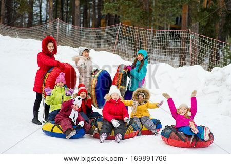 Kids on snow tubes downhill at winter day. Forest on the background