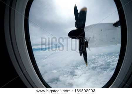 engine and propeller of the plane view from window airplane white clouds and blue sky as background
