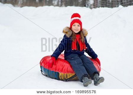Little girl on snow tubes downhill at winter day. Forest on the background