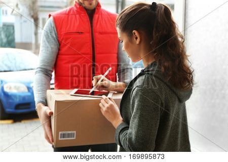 Young woman appending signature after receiving parcel from courier