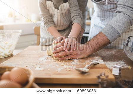 Father and his son preparing bisquits in the kitchen
