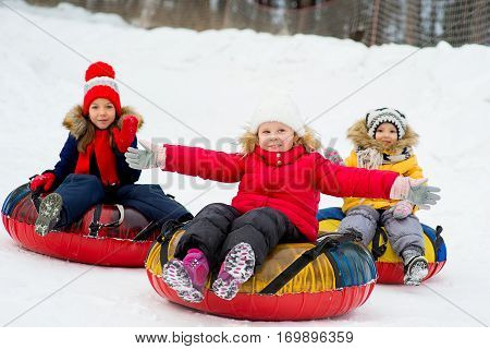 Kids on snow tubes downhill at winter day. Forest on the background. First plan little girl