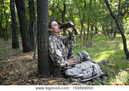 Soldier drinking water from canteen in forest