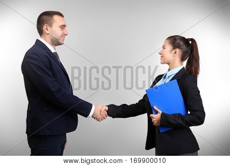 Young man and woman shaking hands on light background