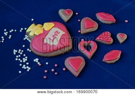 Different form and size heart shaped honey cakes with rose glaze and word love lay on blue background. Focus on word love