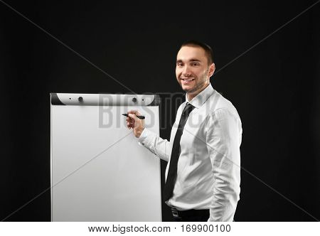 Young businessman standing near flip chart on black background