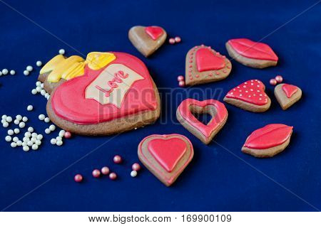Different form and size glazed honey cakes in shape of heart and lips lay on blue background near white and rose small beads. Focus on word love