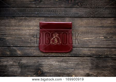 Stylish leather wallet with money and box on wooden background.