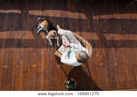 Beautiful senior woman with her dog at home, sitting on rattan chair on wooden terrace, relaxing