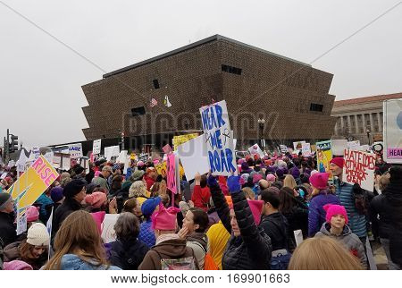 WASHINGTON DC - JAN 21, 2017: Women's March on Washington, marchers pass the African-American Museum in the background, in an anti-inauguration show of solidarity.