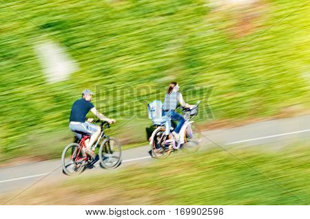 Silhouettes of unrecognizable young family bicycling with mother carrying the little daughter children on the bike child seat and father following them