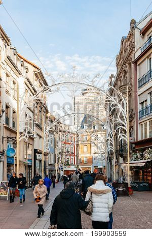 MULHOUSE FRANCE - DEC 12 2015: Shopping street Rue Merciere in central Mulhouse during Christmas Market with people entering shops to buy gifts and food