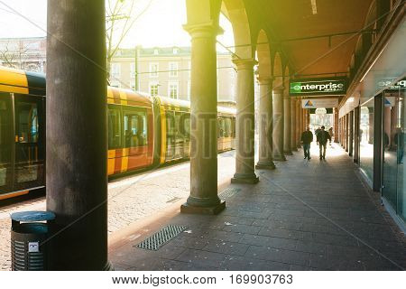 MULHOUSE FRANCE - DEC 12 2016: Tramway passing - view through the beautiful colonnade Arcades on the Avenue du Marechal Foch in central Mulhouse on a warm winter sunny day