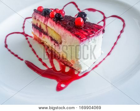 Close up of a slice of berries mousse cake with white cream. Puff pastry, fruits and cream with decorative strawberry jam. Flat lay aerial view. Local italian food.