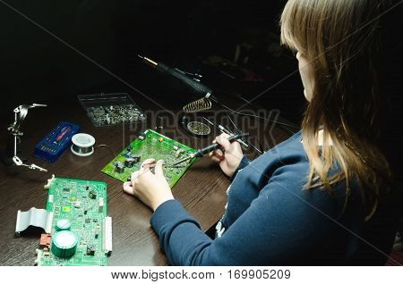 Young woman technician repair electronics device use soldering iron