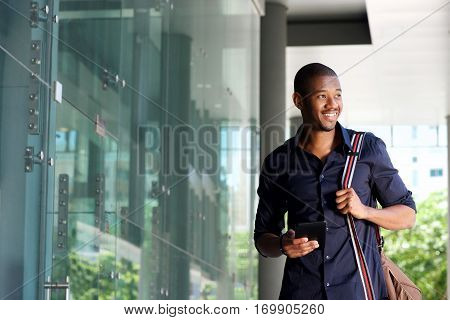 Smiling African Man Walking With Mobile Phone And Bag
