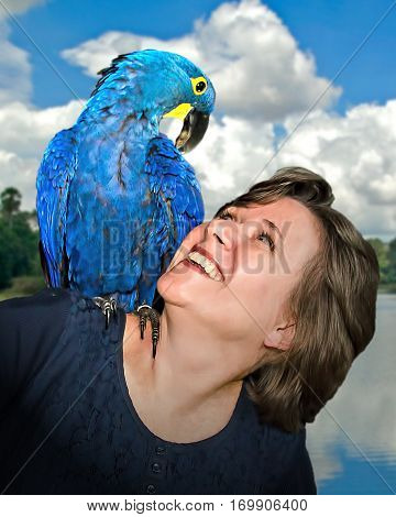 This is a picture of a woman in her 30s or 40s, looking up with a smile on her face at a blue hyacinthine Macaw (a type of parrot) on her shoulder. The parrot stares back at her.