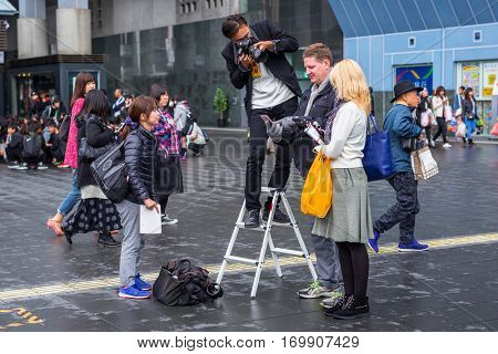 KYOTO, JAPAN - NOVEMBER 10, 2016 : Photographer at work near the railway station in Kyoto, Japan. Kyoto was formerly the Imperial capital of Japan for more than one thousand years.