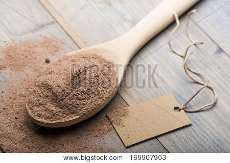 heap cocoa in wooden spoon on table with label for text.