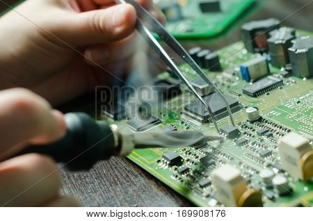 Male hands close up soldering a microchip