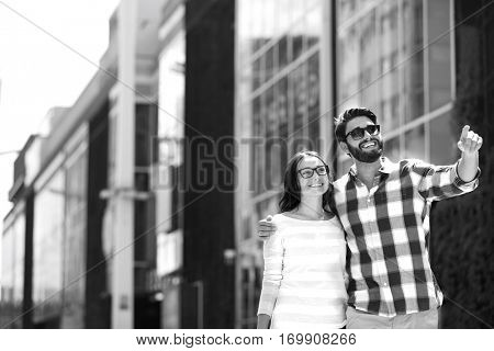 Happy man showing something to woman outside building