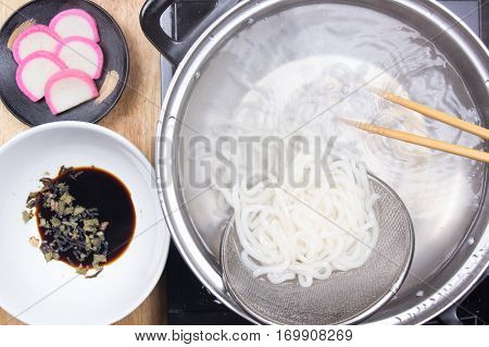 Chef scald udon noodle in pot / Cooking Tempura Udon concept