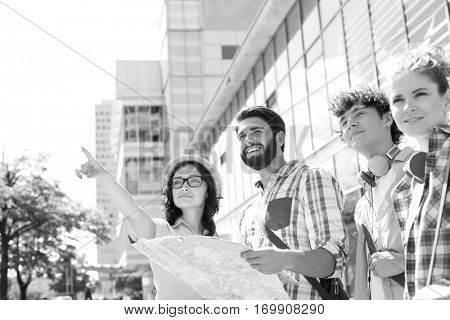 Happy friends with road map with woman pointing away in city