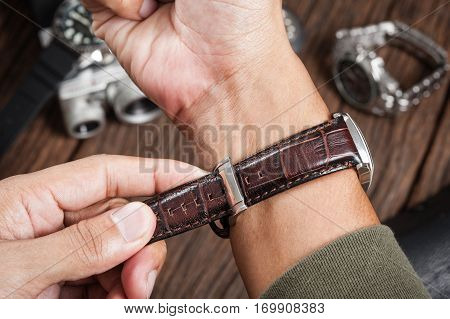 closeup brown leather watch band on man's wrist