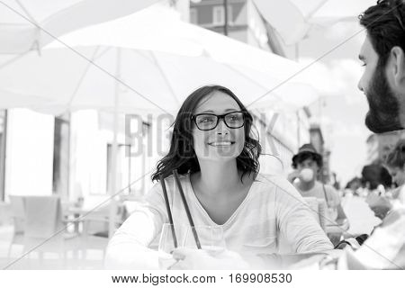 Smiling woman sitting with man at sidewalk cafe