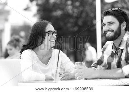 Cheerful couple having mojito at sidewalk cafe