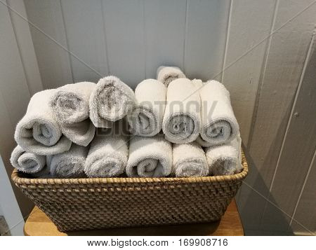 pile of cloth hand towel table napkin handkerchief on the basket with blur white wooden wall background