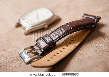 closeup brown leather watch band on brown background