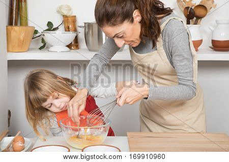 Woman And Child Cooking Stirring An Egg In Bowl