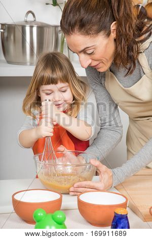 Woman And Smiling Child Whipping To Make A Cake
