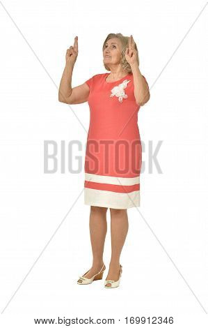 senior woman in coral dress posing on white background