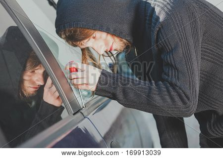 Anti theft system problem concept. Thieft man dressed in black holding screwdriver trying to break into car