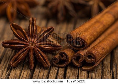 Star anise and cinnamon on old wooden table. Selective focus.